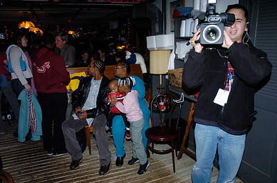 A family of four waits its turn to be seated at Stroud's as a tv station photographer tapes this photographer at work.