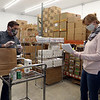 Volunteers Jeanne Urda and Rick Bailey, both of Townsend, pack bags and boxes of food for seniors and families in need, at the Townsend Ecumenical Outreach food bank. Clients check off on a list which items they need.  (SUN/Julia Malakie)