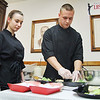 """Leominster High School culinary arts seniors Brittany Peterson and Erica Peltola get some olive bread cut to go with the Curry Pumpkin soup and caesar salad they where serving up at the """"Taste of Leominster"""" on Wednesday night at City Hall. SENTINEL & ENTERPRISE/JOHN LOVE"""