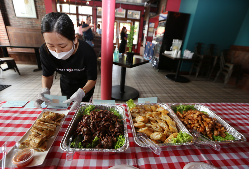 Opening of Tasty Dumplings, new restaurant on Market Street at Cardinal O'Connell Parkway. Meili Jin of Concord, a friend of the owner who was helping, labels dishes. From left: Scallion Pancakes, Beef Mini Skewers, Pork Egg Rolls, and Chicken Mini Skewers. (SUN/Julia Malakie)
