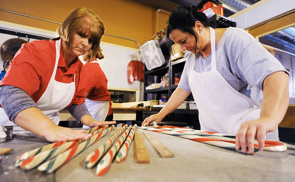 Minerva Candy Co. in Webb City employees Jackie Filarski (left) and Karen Steele keep rolling candy canes as they cool and shaping the crooks Saturday afternoon, Nov. 23, 2013.<br /> Globe | T. Rob Brown