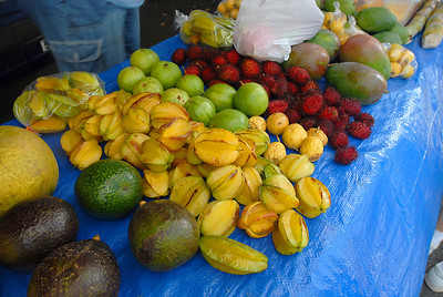Farmer's fruit stand with lots of fresh ripe organic tropical fruits for sale: star fruit and lichi.