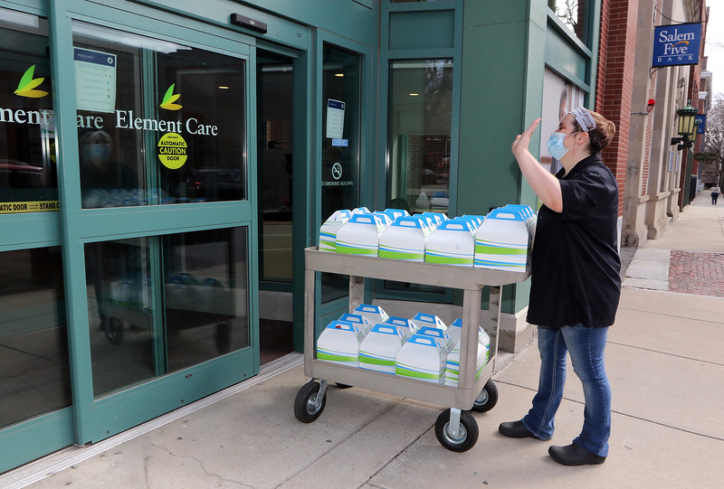 UTEC employees put together meals and weekly food boxes for distribution. Cafe program manager Kassandra Berzins of Manchester, N.H., walks lunch and dinner cartons from UTEC to Element Care and the Recovery Cafe, for those organizations to distribute to individuals. JULIA MALAKIE/LOWELLSUN