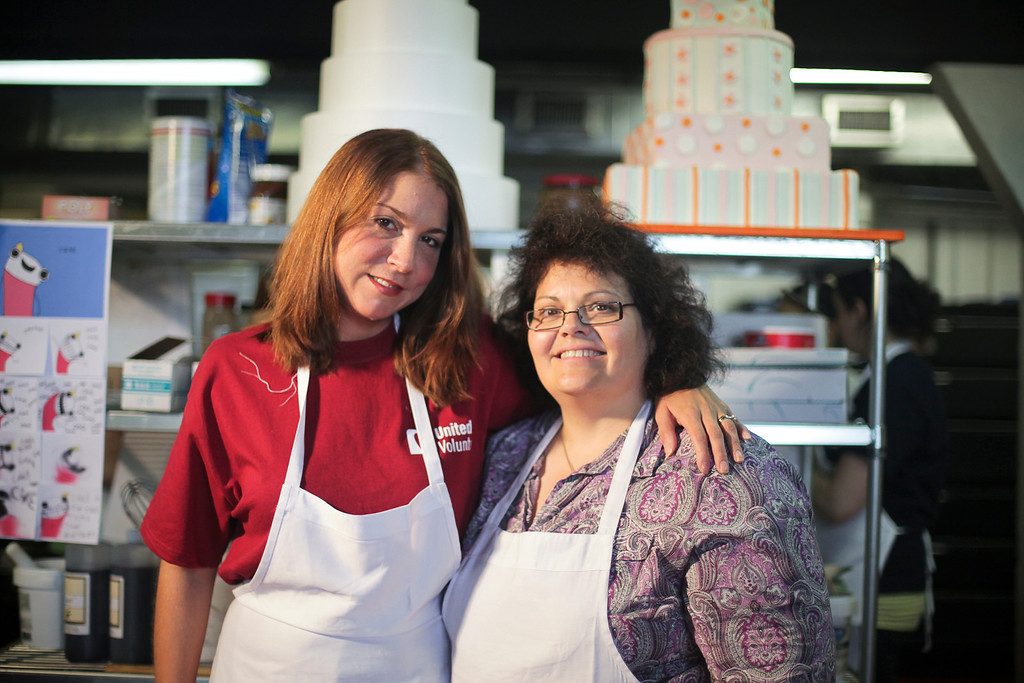 At Sin, a Custom Cake Company in Providence,  United Health Care Senior Network Account Mgr. Jennifer Macaluso (in purple w/ glasses) and Administrative Assistant, Barbara Finn (in red) mold fondant into the white rose buds that will adorn a Mardi Gras themed sweet sixteen birthday cake United in donating to the Make-a-Wish Foundation. (Photo by: Ryan T. Conaty)