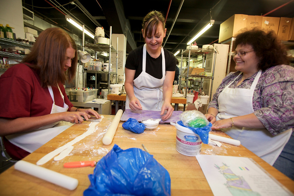 Under the supervision of Sin owner, Jennifer Luxmoore, United Health Care Senior Network Account Mgr. Jennifer Macaluso (in purple w/ glasses) and Administrative Assistant, Barbara Finn (in red) mold fondant into the white rose buds that will adorn a Mardi Gras themed sweet sixteen birthday cake United is donating to the Make-a-Wish Foundation. (Photo by: Ryan T. Conaty)