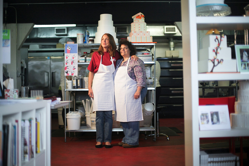 At Sin, a Custom Cake Company in Providence,  United Health Care Senior Network Account Mgr. Jennifer Macaluso (in purple w/ glasses) and Administrative Assistant, Barbara Finn (in red) mold fondant into the white rose buds that will adorn a Mardi Gras themed sweet sixteen birthday cake United is donating to the Make-a-Wish Foundation. (Photo by: Ryan T. Conaty)