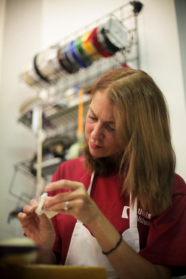 United Health Care Administrative Assistant, Barbara Finn molds fondant into the white rose buds that will adorn a Mardi Gras themed sweet sixteen birthday cake United is donating to the Make-a-Wish Foundation. (Photo by: Ryan T. Conaty)