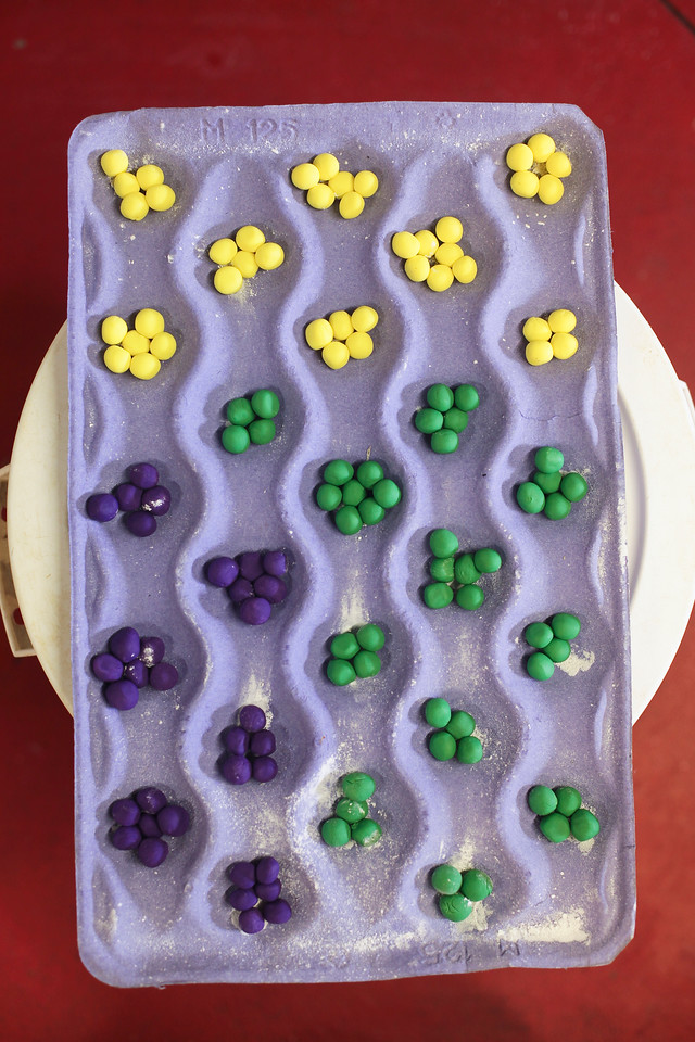 At Sin, a Custom Cake Company in Providence, colored fondant beads await placement on the Mardi Gras themed sweet sixteen birthday cake United Health Care is donating to the Make-a-Wish Foundation. (Photo by: Ryan T. Conaty)