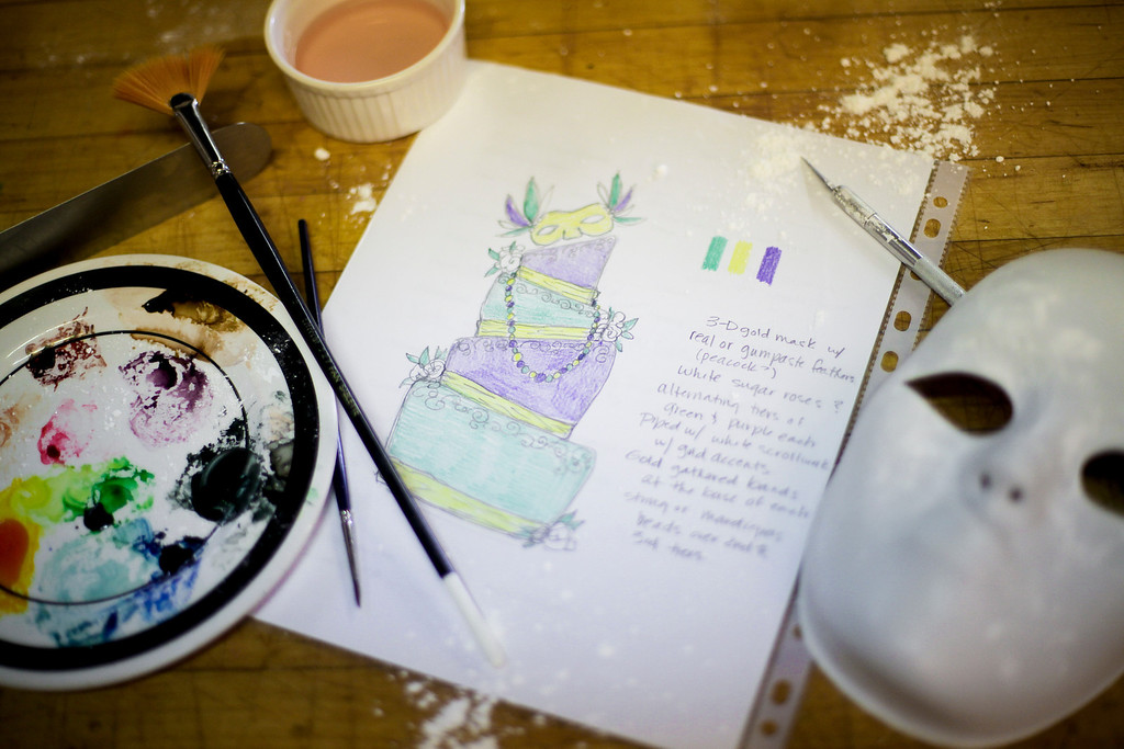 At Sin, a Custom Cake Company in Providence,  United Health Care volunteers follow an illustration of a Mardi Gras themed sweet sixteen birthday cake United is donating to the Make-a-Wish Foundation. (Photo by: Ryan T. Conaty)