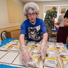 Seamus Leger piles food packages during the United Way Heroes Against Hunger event sponsored by the Town and Country Apartments owner Marc DiGeronimo on Tuesday morning. SENTINEL & ENTERPRISE / Ashley Green
