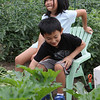 Dohyun Yoon, 9, and and his sister Dana Yoon, 6, share a small chair in their family's plot at the Westford Community Garden. (SUN/Julia Malakie)