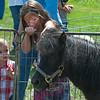 Connor Sitterly, 1, of Brookfield watches as Juliana Senn, 6 of Reading pats a small pony at the Wachusett Mountain Farm Fresh Festival. SENTINEL&ENTERPRISE/ Jim Marabello