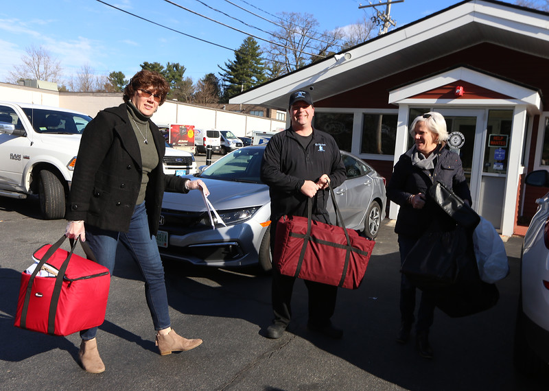Wilmington Council on Aging director Terri Marciello, left, and case manager Laura Pickett, pick up breakfast sandwiches donated by AJ's Kitchen owner David Erickson of Wilmington, center, to be delivered to seniors who normally just get meals delivered Monday to Friday. (SUN/Julia Malakie)