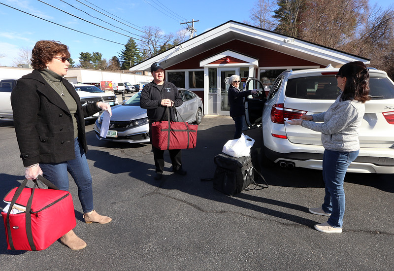 Wilmington Council on Aging director Terri Marciello, left, case manager Laura Pickett, rear, and volunteer Christine Nally of Wilmington, right, pick up breakfast sandwiches donated by AJ's Kitchen owner David Erickson of Wilmington, center, to be delivered to seniors who normally just get meals delivered Monday to Friday. (SUN/Julia Malakie)