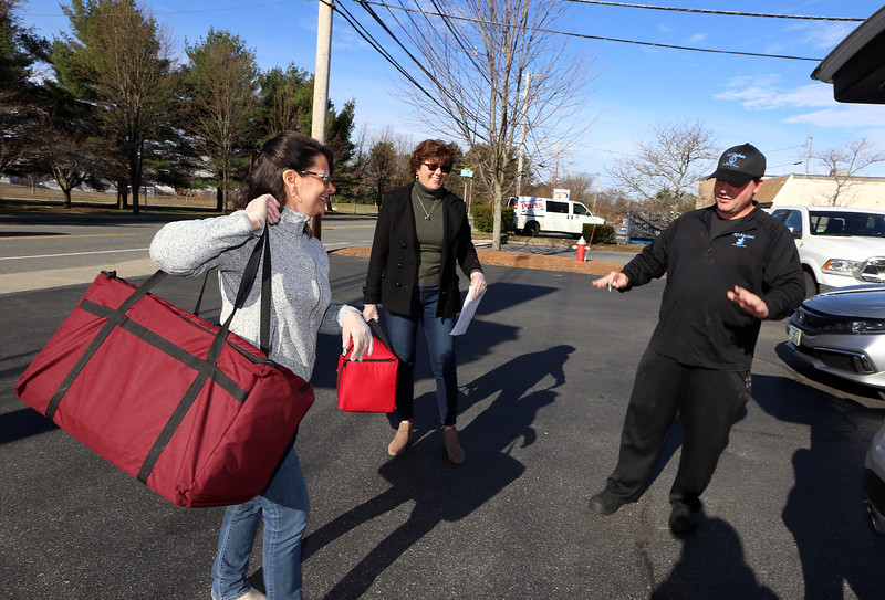 Wilmington Council on Aging volunteer Christine Nally of Wilmington, left, and director Terri Marciello, case manager Laura Pickett, and  pick up breakfast sandwiches donated by AJ's Kitchen owner David Erickson of Wilmington, to be delivered to seniors who normally just get meals delivered Monday to Friday. (SUN/Julia Malakie)