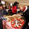 Wilmington-Tewksbury United Methodist Women hold their third annual Chocolate Festival, a fundraiser for local organizations that help women and children. Church member April Kingston of Billerica, right, helps Benjamin Gavegnano, 9, of Wilmington.  (SUN/Julia Malakie)
