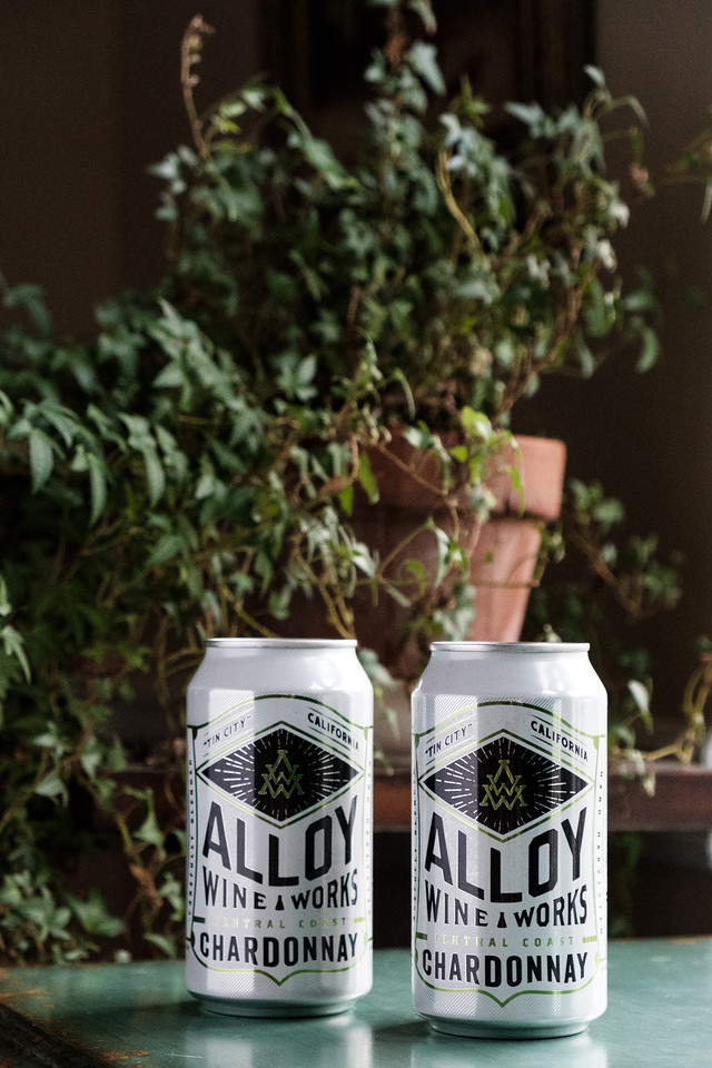 two cans of Ally Wine Works chardonnay in front of a plant