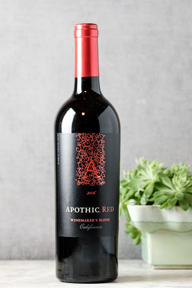 Bottle of Apothic Red Winemaker's Blend in front of a plant