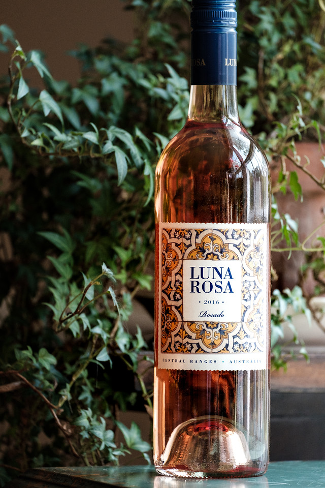 Bottle of 2017 Luna Rosa in front of a plant