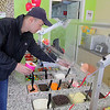 Co-owner of  Froyo 4U in Leominster Johnny Huynh shows how to put toppings on your yogurt at his place on Saturday. SENTINEL & ENTERPRISE/JOHN LOVE