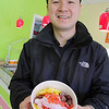 Co-owner of  Froyo 4U in Leominster Johnny Huynh shows shows off a finished yogurt with a few toppings at his place on Saturday. SENTINEL & ENTERPRISE/JOHN LOVE