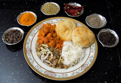 Traditional Indian spices (from left) Cardamom, turmeric powder, coriander seeds, red pepper kushmari mirch, cumin seeds, cloves, surround a dish of chicken Tikka Misaki, basmati rice, chickpeas and fried bread.