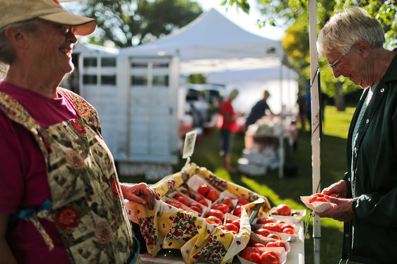 Jackie Taylor, left, of Happy Jack Harvest laughs with Doris Eyestone as she sells her some fresh tomatoes Thursday, September 19, 2019 at theThursday Locals Market. Nadav Soroker/Laramie Boomerang