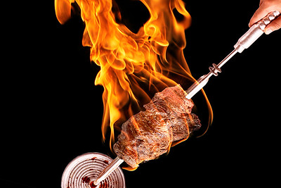 Meat on a skewer on fire