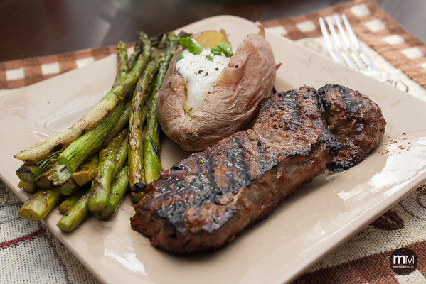 Dinner: perfectly cooked New York Strip steaks with grilled asparagus and baked potato.
