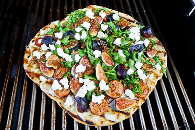 Immediately move pizza dough to cooler side of grill and add toppings, quickly, but don't get burned from that heat coming off the grill. Add grated fontina, then the spicy Italian sausage, red oinions, figs, and balsalmic vinaigrette. Put the top down to get more heat on the toppings, about 3-4 minutes.  Add arugula and goat cheese (Laura Chenel) and cover for a minute or so and then serve.  This is a different routine than what you do with the baking stone, where almost everything goes on at the beginning. Stay focused and use your judgement.