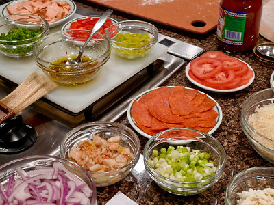 Mis en place: all ingredients prepped and ready for a run of four different pizzas. Note spicy oil with pepper flakes, pre-sauteed shrimp pieces and flaked smoked salmon.