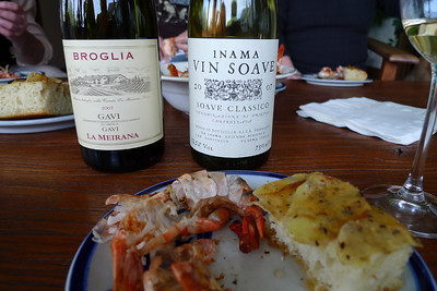 Grilled shrimp and my homemade potato-rosemary foccacia accompany an array of wines at a dinner gathering at a close friend's house. Only two of the many are pictured here.