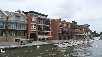 Scenic wide angle view of the River Thames at Windsor with luxury flats on one side, foot bridge to connnect Eton with Windsor and Castle on other side. Windsor, Berkshire, England, UK