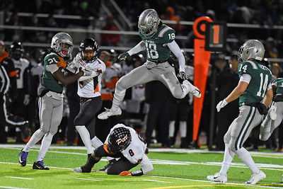 De La Salle's Charles McAdoo (18) leaps over Pittsburg's  Avant Muldrow (8) after being tackled to the ground in the first quarter of their North Coast Section Division I football championship game at Dublin High School in Dublin, Calif., on Friday, Nov. 29, 2019. De La Salle defeated Pittsburg 49-7 to win it's 28th consecutive NCS title. (Photo by Jose Santos Fajardo)