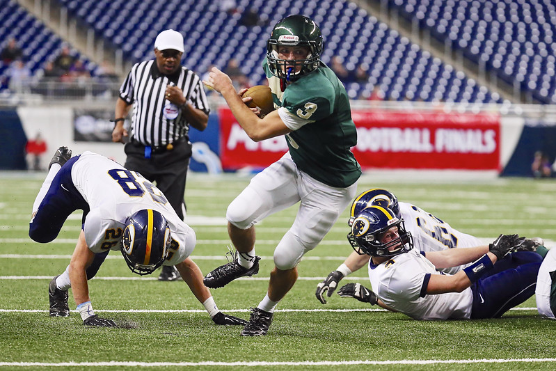 Zeeland West QB #3 Casey Brinks leaves 3 Dewitt Panthers defenders sprawling on the ground as he carries the ball around end.