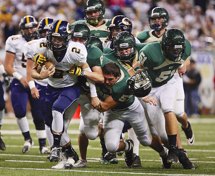 A host of the Zeeland West defense tackles the Dewitt ball carrier as #57 TJ Langeland's helmet comes flying off.
