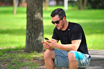 Gatorcountry football writer Nick De La Torre gets some work done from his phone prior to the start of  Friday Night Lights.2014 Friday Night Lights.  July 25th, 2014. Gator Country photo by David Bowie.