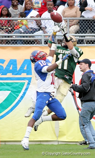 Johnny Lawroski of Trinity Catholic attempts to haul in a pass from QB Rob Henry, with DB Merrill Noel of Pahokee providing coverage on the play during third-quarter action of the FHSAA Class 2B final on December 13, 2008.