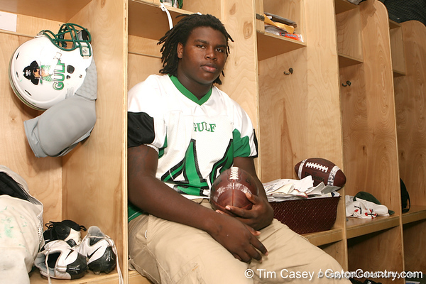 New Port Richey (Gulf HS) defensive tackle Leon Orr poses next to hundreds of recruiting letters that haven't been opened on Sept. 23, 2009 at Gulf High School in New Port Richey, Fla. / Gator Country photo by Tim Casey