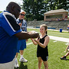 Kaleigh Fuller, 8, receives a football for her hard work from Leominster High coach Mike Austin during football camp at Doyle Field on Friday morning. SENTINEL & ENTERPRISE / Ashley Green