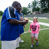 Halle Kendall, 6, receives a football for her hard work from Leominster High coach Mike Austin during football camp at Doyle Field on Friday morning. SENTINEL & ENTERPRISE / Ashley Green