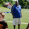 Leominster High coach Mike Austin looks on as kids participate in drills during football camp at Doyle Field on Friday morning. SENTINEL & ENTERPRISE / Ashley Green