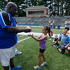 Sophia Borges, 7, receives a football for her hard work from Leominster High coach Mike Austin during football camp at Doyle Field on Friday morning. SENTINEL & ENTERPRISE / Ashley Green