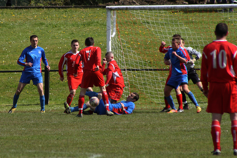 A Carluke centre forward goes down under a challenge from John Yule, and yet another penalty is given against Burgh