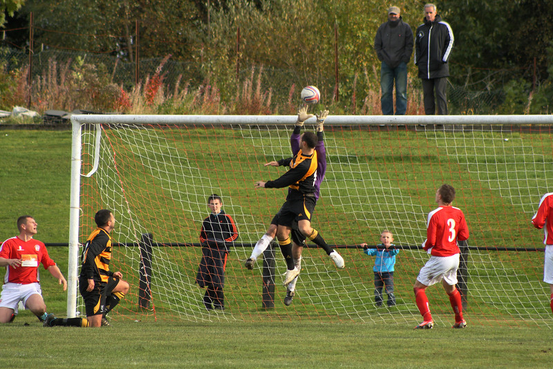 Fraser Wilson bundled out of the way when going for this high ball