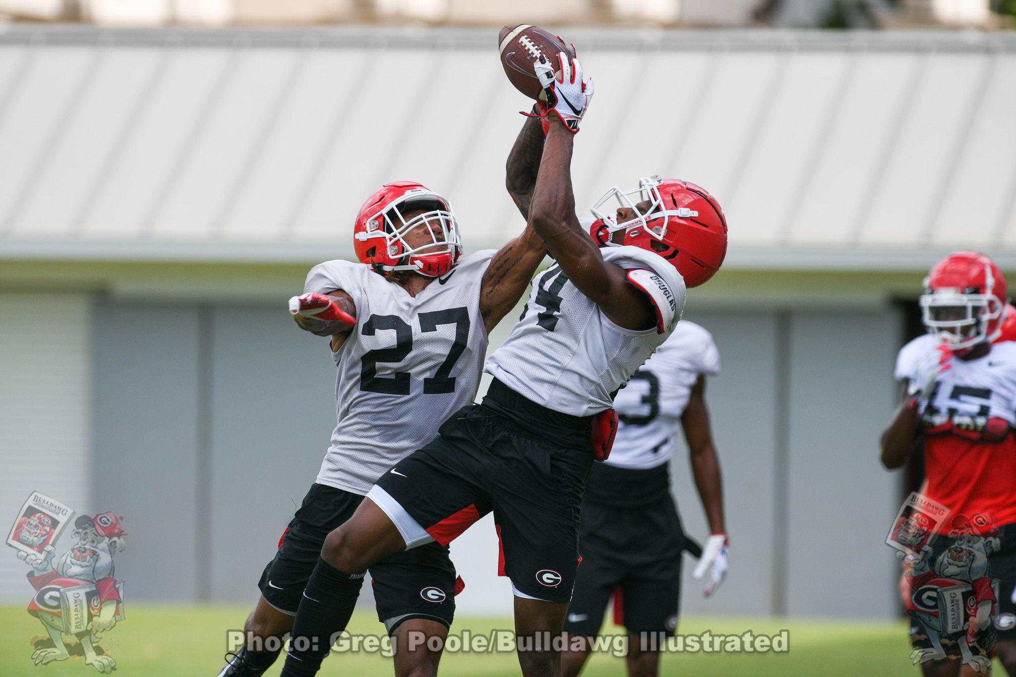 Eric Stokes (27) and Matthew Brown (24) participate in tip drills during practice.