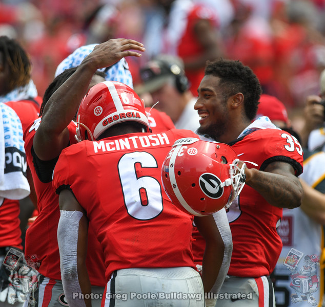 Bulldog running backs celebrate with fellow tailback Kenny McIntosh (6) after his TD
