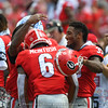 Other running backs greet Kenny McIntosh (6) after his TD