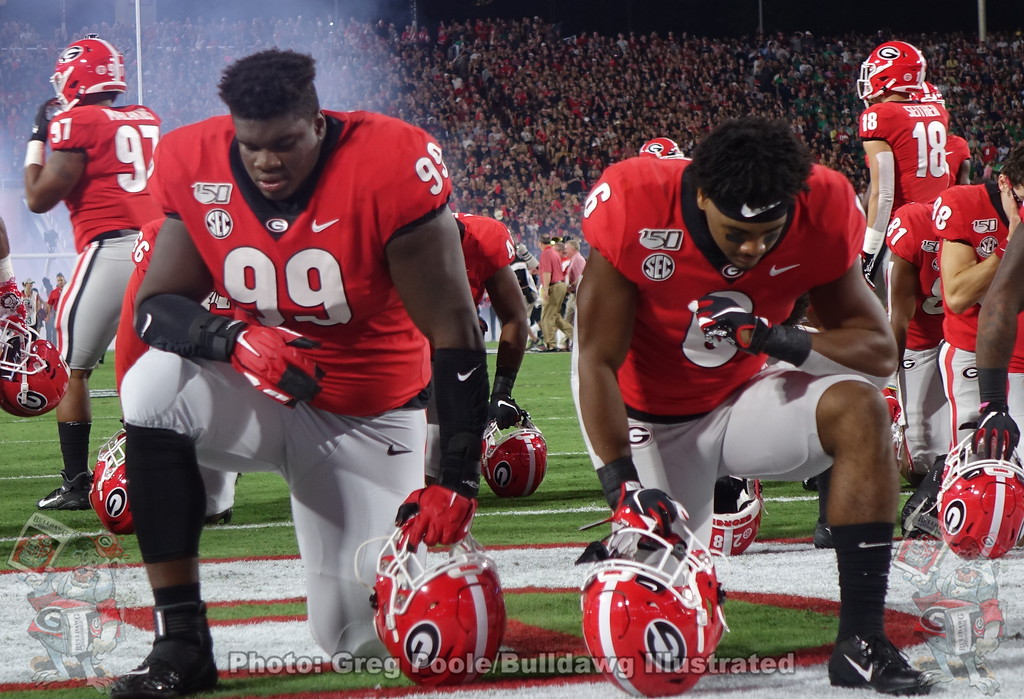 Jordan Davis (99) and Kenny McIntosh (6) take a knew before the game versus Notre Dame, Saturday night, September 21, 2019