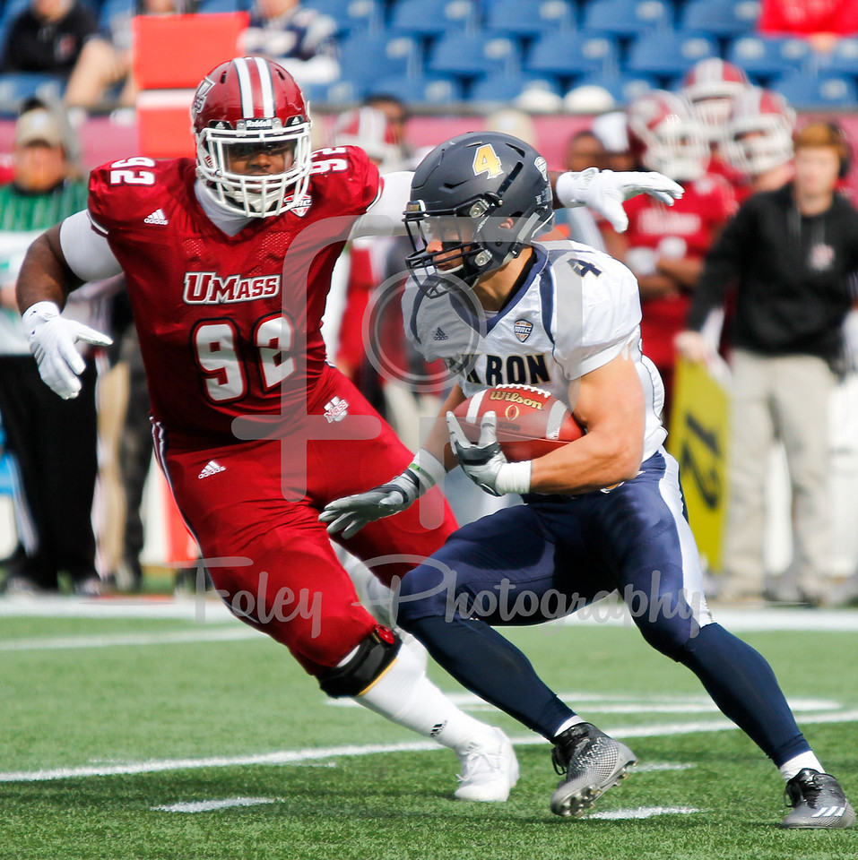@ZipsAthletics running back Conor Hundley tries to get away from @UMassFootball Robert Kitching during a @Macsports conference matchup.